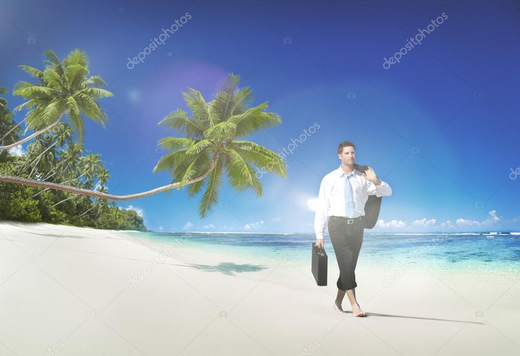 man in suit walking at beach