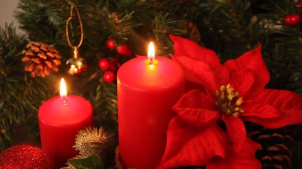 Weihnachtskerze mit Dekoration brennt hell.