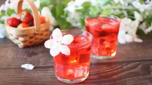 Erdbeer-Limonade mit Eiswürfel. Frau legte Hand in Hand einen Zweig mit weißen Apfelblüten. Frühjahrskonzept.
