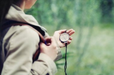woman discovering nature and checking directions with compass in