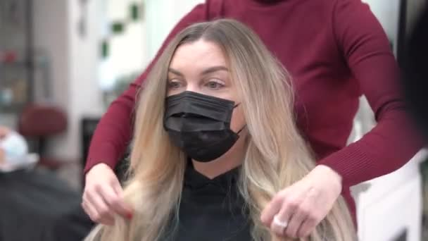 in a beauty salon hairdresser straightens long blonde hair to a girl. girl sitting in a protective mask