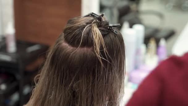 egy szépségszalonban egy fodrász egy hajtűvel rögzíti a nedves haj tetejét. az alsó részt megfésülik