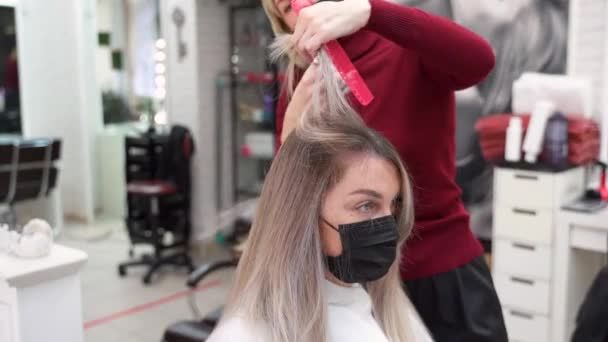 a hairdresser in a beauty salon cuts long blonde hair with scissors to a girl who sits in a black protective mask