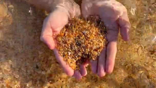 a férfi tenyér közelsége, amelyben a tenger durva homok vagy kagyló sziklája és hullámai elmosódnak és felborítják
