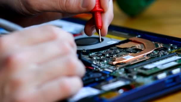 Ein Mann arbeitet mit einem Multimiter, misst Spannung und Widerstand, misst die Parameter einer Laptop-Mikroschaltung. Nahaufnahme. Reparatur von Geräten.
