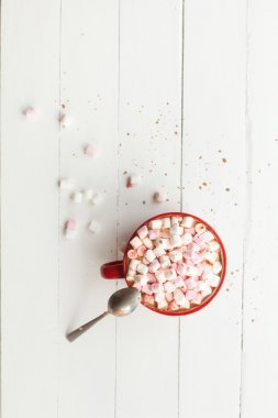 Hot chocolate with marshmallows in red cup on table