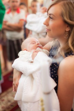Little girl on ceremony of child christening