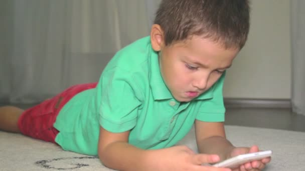 Caucasian boy plays game on phone.