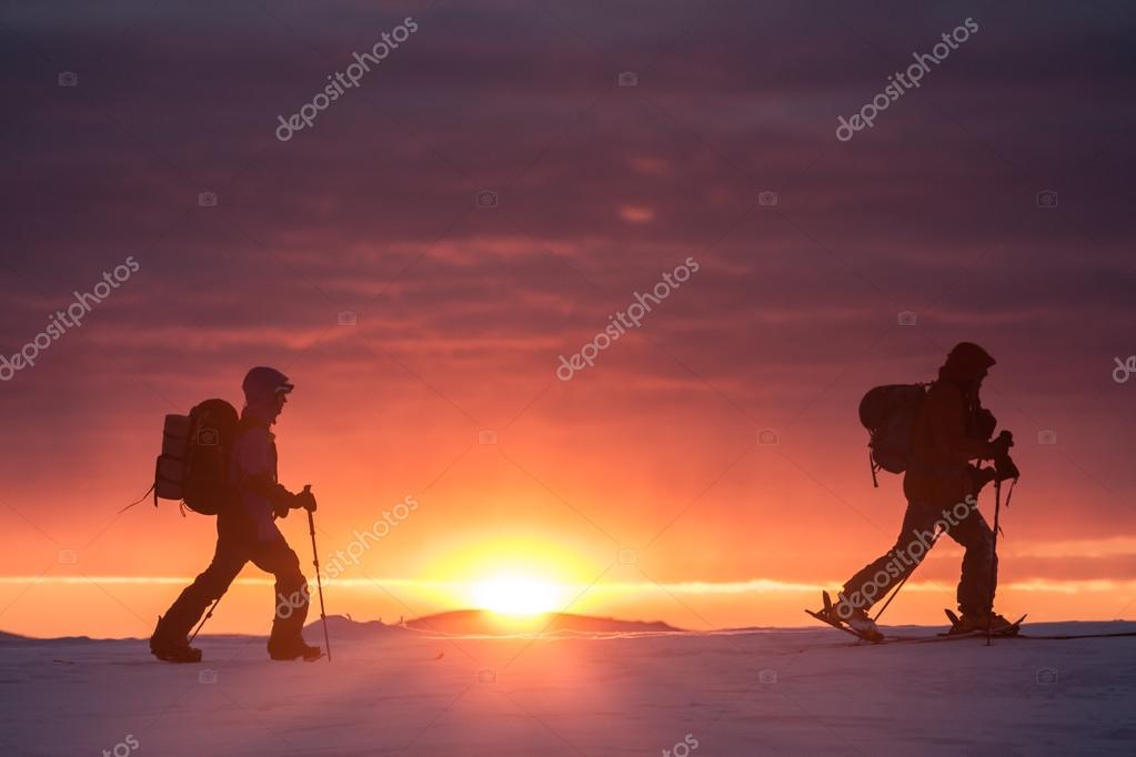 Two skiers walking mountains against sunset