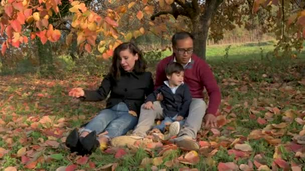 Family closeup medium-shot in a park during Autumn season. People smiling , parents holding son in the middle. Happiness, togetherness, childhood concept.