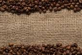 Fotografie Roasted coffee beans stripes on burlap texture