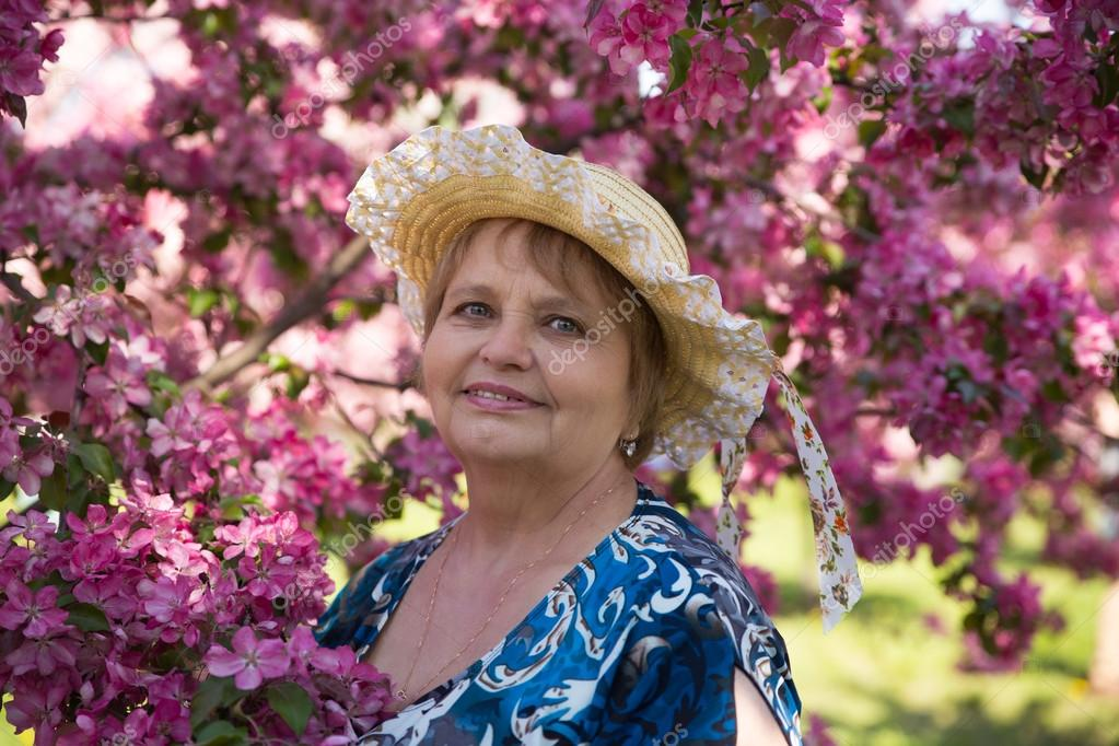 adult woman in hat under pink flowers trees