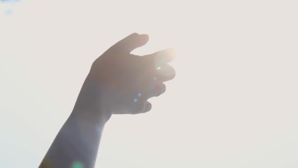 Dívčí ruka na pozadí slunce. Prsten na ženské ruce. The lights of a sun