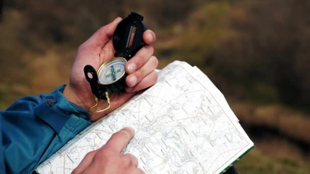 Man tourist in a blue jacket looking on the compass and map