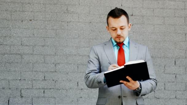 Kaukasischer Geschäftsmann schreibt im Freien in Notizblock