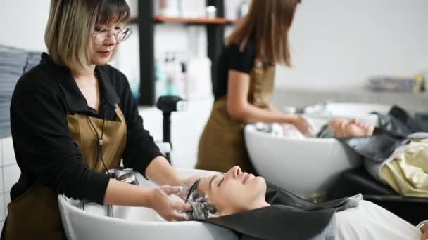 A hairdresser washes hair for a customer in a salon shop and women lying on a chair in a robe which takes care of the hair and scalp professionally.