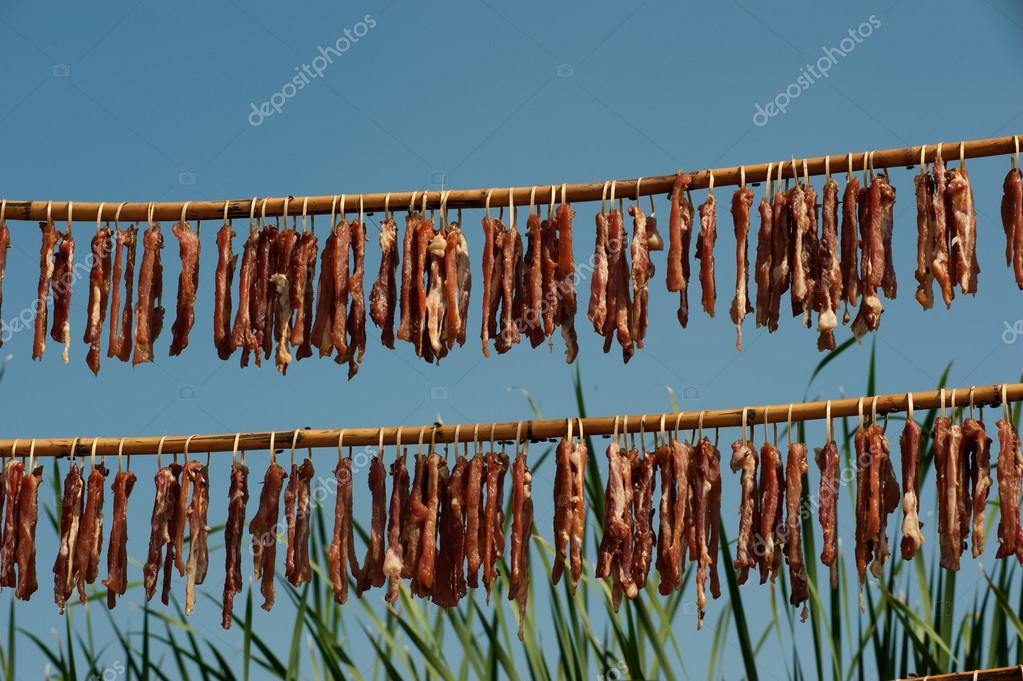 Meats drying in the sun .