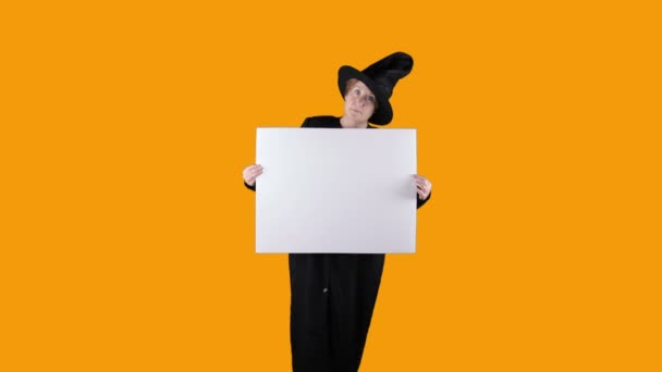 Halloween čarodějnice s bílou cedulí na oranžové obrazovce