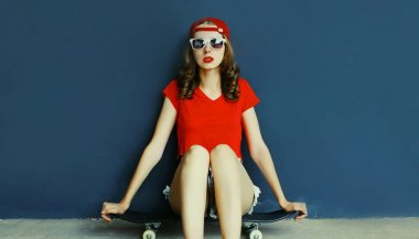 Girl sitting on skateboard wearing baseball cap over blue wall background
