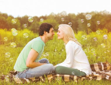 Pretty romantic couple in love having fun soap bubbles