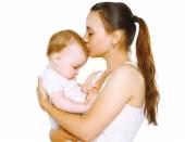 Fotografie Sinnliche Mutter Kuss Baby auf weißem Hintergrund