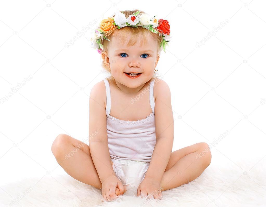 Schattige baby meisje met bloemen krans op zijn hoofd vreugdevolle