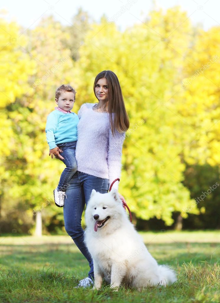 Young mother and child walking with white Samoyed dog in the par