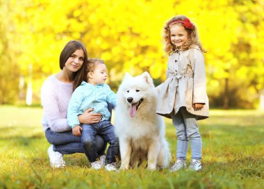 Family portrait, pretty young mother and children walks with dog