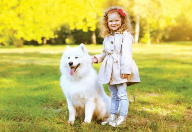 Happy laughing child and dog having fun outdoors in warm autumn