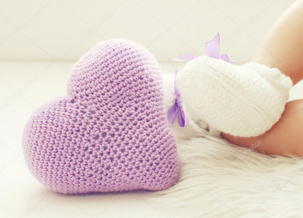 f6ad7216c17 Πλεκτά baby καρδιά και τα πόδια στο λευκό παντόφλες του μωρού — Φωτογραφία  Αρχείου