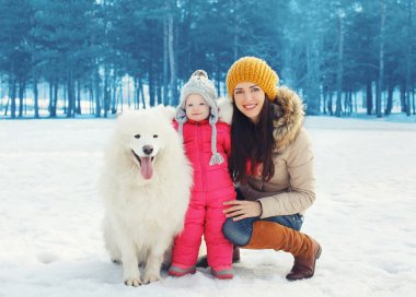 Portrait of happy family in winter day, mother and child walking
