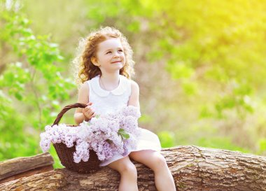 Little girl with basket of lilac flowers sitting and enjoying su