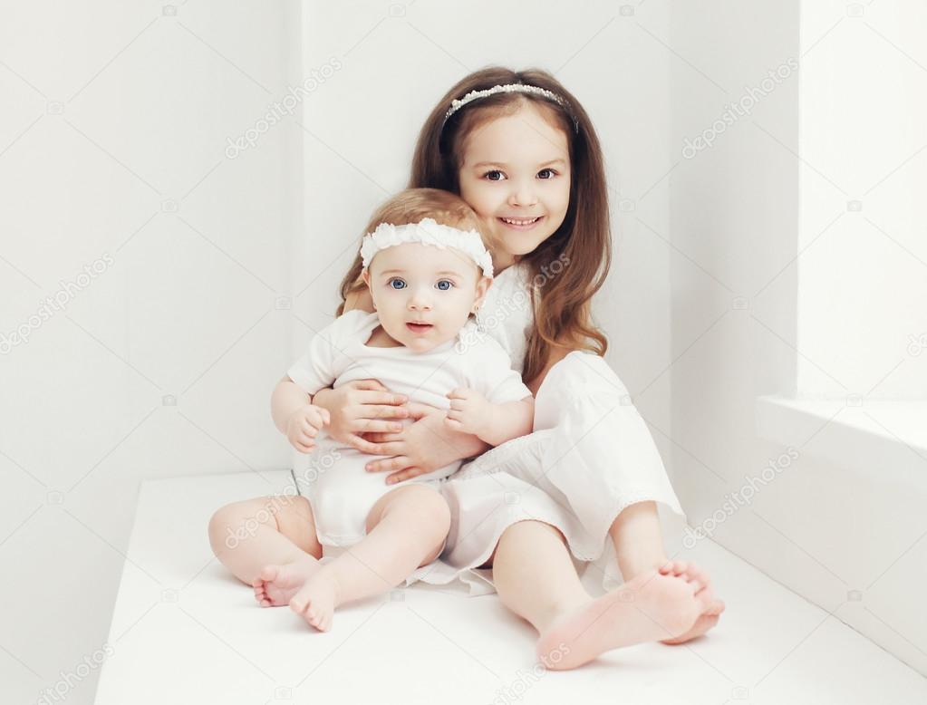 маленькие девочки Две сестры, маленькие девочки в белом зале дома возле окна — Фото автора  Rohappy