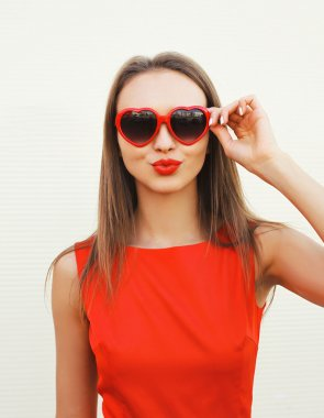 Portrait of pretty woman in the red sunglasses blowing lips havi