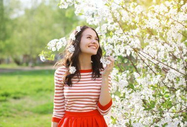 Beautiful smiling young woman enjoying smell flowering spring ga