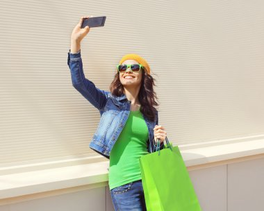 Fashion happy pretty cool young woman with shopping bags makes p