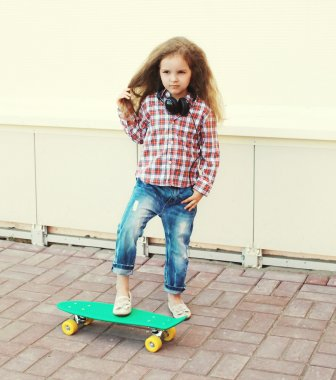 Fashion kid concept - stylish little girl child with skateboard