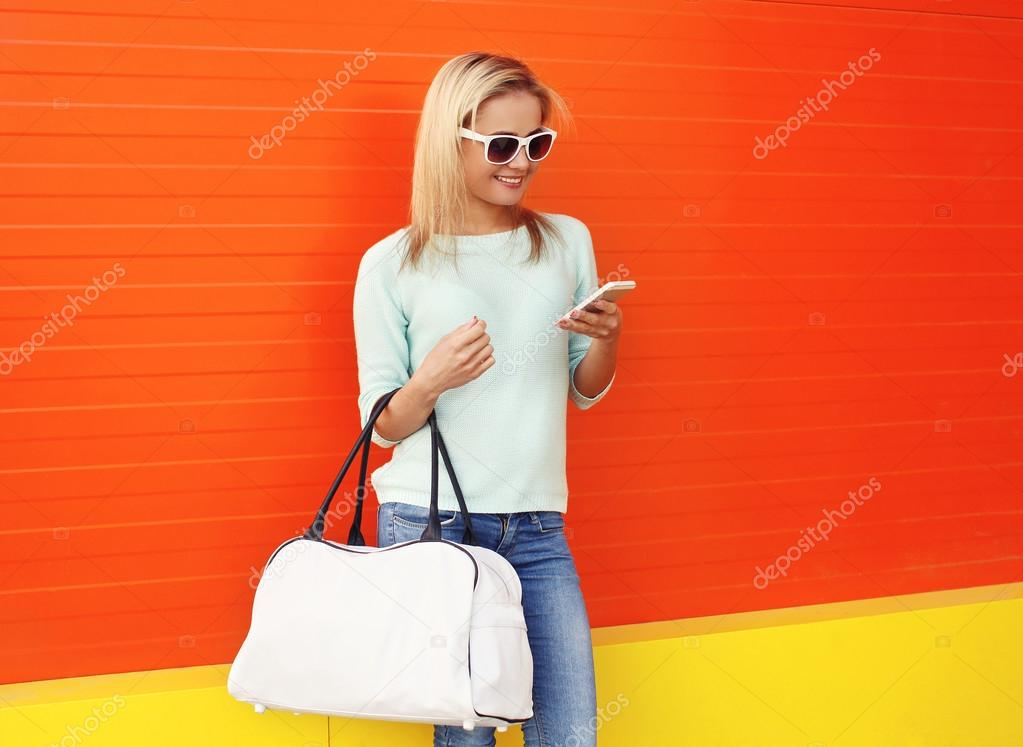 Fashion portrait of pretty smiling woman in sunglasses with bag