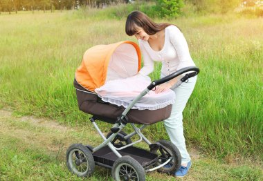 Happy young smiling mother walking with baby stroller outdoors o