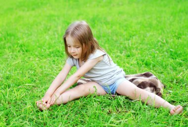 Little girl child sitting on the grass does yoga stretching exer