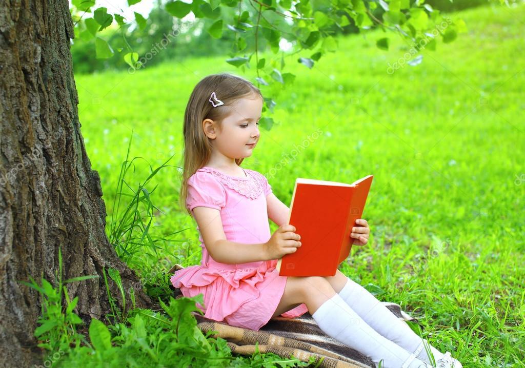 Pequeña Niña Leyendo Un Libro En El Césped Cerca De