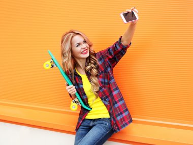 Pretty smiling blonde young woman in colorful clothes with skate
