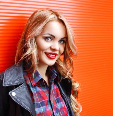 Portrait of pretty smiling blonde woman with red lips over red b