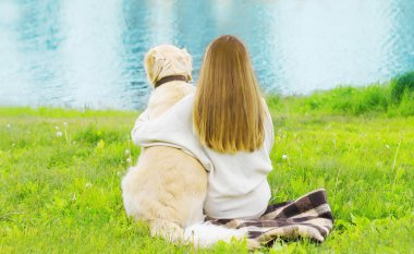 Silhouette of owner and Golden Retriever dog sitting together on