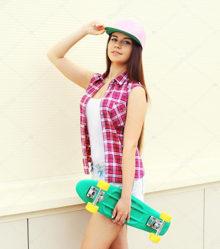 5464d930e6 Fashion hipster cool girl in colorful pink clothes with skateboard having  fun outdoors over white wall — Zdjęcie od Rohappy. Znajdź podobne obrazy