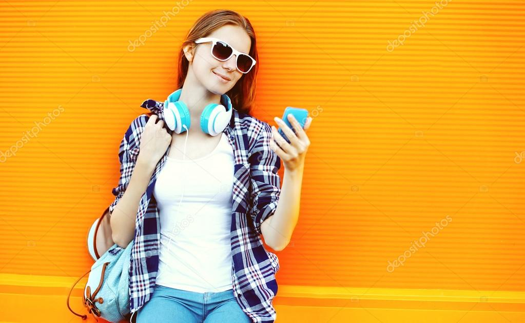 Pretty girl in sunglasses and headphones using smartphone agains