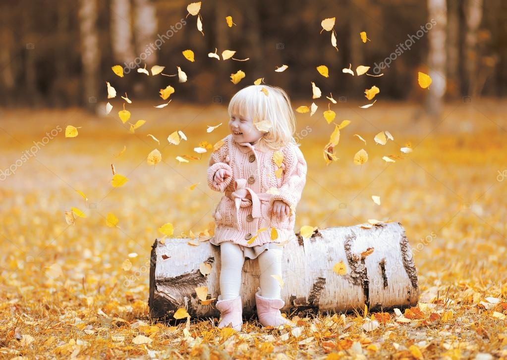 Happy child throws up yellow leaves and having fun in autumn par