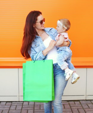Beautiful smiling mother holding on hands baby with shopping bag