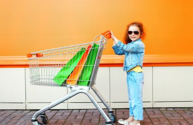 Happy little girl child with trolley cart and colorful shopping