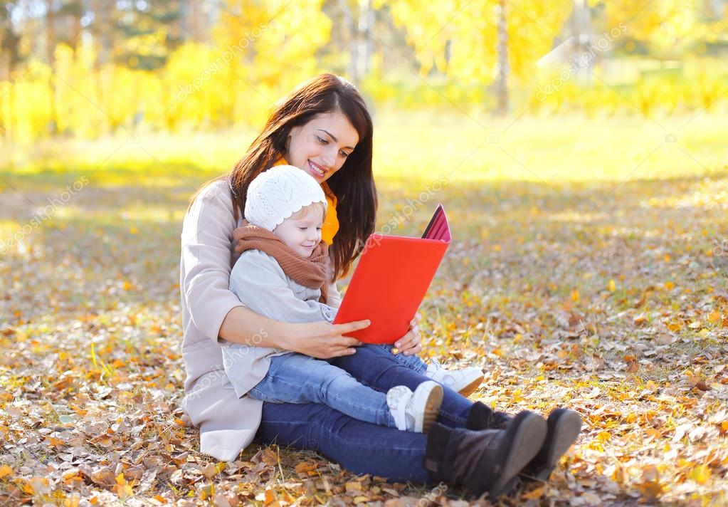 Mother and child looking on book or tablet pc sits together on l